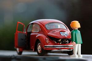 Kleiner Käfer mit offener Motorklappe und davor stehendem Playmobil Männchen