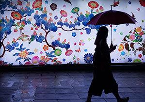 Frau mit Automatik-Schirm im Hintergrund Wand mit Graffiti