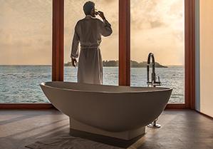 Mann steht hinter einer weißen stylischen Badewanne, im weißen Bademantel an einer Fensterfront und im Hintergrund Meer