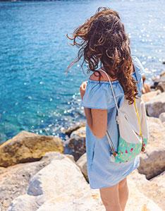 Frau mit langen braunen Haaren steht auf Felsen und schaut auf das türkis farbene Wasser und trägt einen Sportrucksack