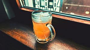 Volles Bierglas auf einer Holz-Fensterbank