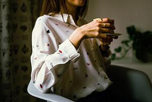Frau mit weißer Bluse und Kaffeetasse in der Hand