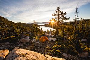Zelten mitten im Wald zwischen Bäumen im Sonnenuntergang