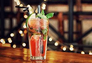 Drink mit Limette, Eiswürfel und Minze in einem Glas und zwei Röhrchen