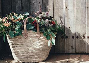 Geflochtene Einkaufstasche voll mit verschiedenen Blumen