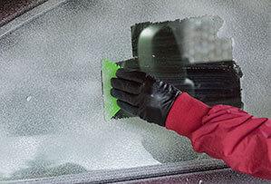 Gefrorene Auto-Scheibe mit Eiskratzer frei kratzen
