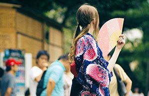 Frau mit luftigem Gewand hält einen Fächer mit orange, rosa und gelben Farbtönen in der Hand
