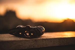 Fernglas liegt auf Stein im Sonnenuntergang