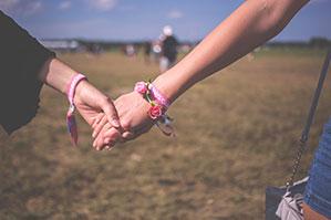 Pärchen hält sich an den Händen, wo Armbänder zu sehen sind