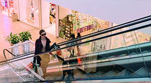 Frau auf der Rolltreppe stehend mit mehreren Einkaufstaschen