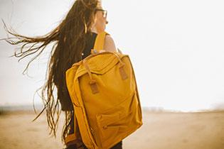 Eine Frau mit langen braunen Haaren steht mit dem Rücken zum Betrachter und trägt einen senfgelben Rucksack