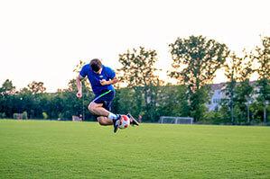 Fußballer mach Kunststück mit Fußball auf Rasen