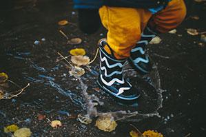 Kind trampelt mit Gummistiefeln in Pfütze