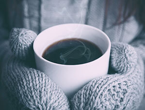 Mit Handschuhen an einer warmen Kaffeetasse aufwärmen