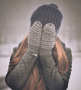 Frau hält Handschuhe vor das Gesicht