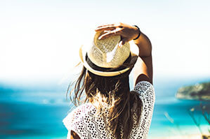 Frau mit Strohhut am Strand