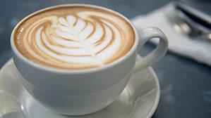 Kaffeetasse mit Unterteller und Milchschaum Baum verziert