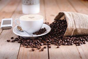Kaffetasse mit Untersetzer und ausgeschütteten Kaffeebohnen