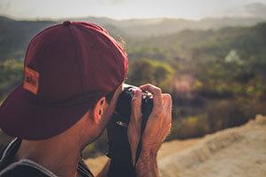 Mann mit dunkelroter Kappe, fotografiert Landschaft