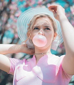 Frau mit Hut und rosa T-shirt macht eine große Blase mit rosa Kaugummi