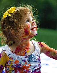 Kleines Mädchen mit Schleife im Haar verschmiert mit Farbe