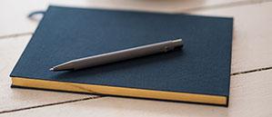 Dunkelgrauer Kugelschreiber liegt auf Buch