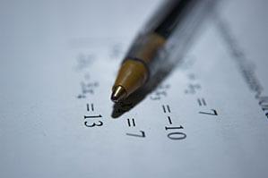 Kugelschreiber mit goldener Spitze liegt auf Zahlen Papier