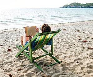 Eine Frau im Liegestuhl liest am Strand in der Sonne ein Buch
