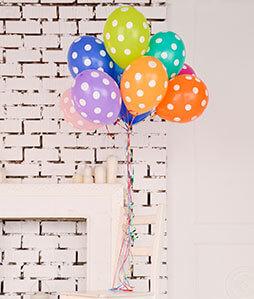 Bunte Luftballons mit weißen Punkten an einem Faden