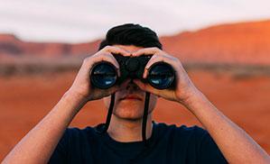 Mann schaut in ein Fernglas mit Umhängeband
