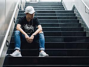 Mann sitzt auf Treppe und hört Musik mit Kopfhörern
