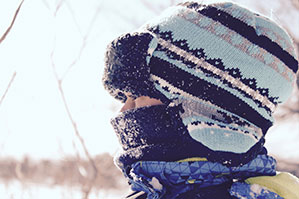 Eine Frau mit Dicker Mütze und dickem Schal eingepackt im Winter