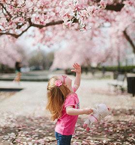 Kleines Mädchen mit pinkem T-Shirt hält eine Plüschtier in der Hand