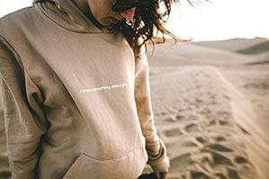Beiger Pullover mit Aufschrift, Sand im Hintergrund