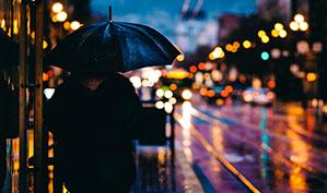 Regenschirm bei Nacht an beleuchteter Straße
