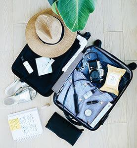 Ein voller Koffer mit Reise-Zubehör, Strohhut, Geldbeutel und Block