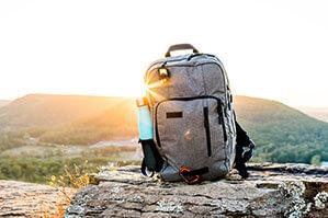 Grauer Rucksack mit Hellblauer Trinkflasche steht auf Felsen im Sonnenuntergang