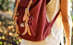 Eine Frau im top mit einem weinrotem Rucksack mit beigen Schnallen