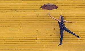 Eine Frau fliegt mit einem Stockschirm vor einer gelben Wand