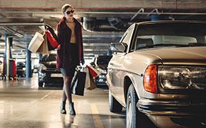 Frau mit vielen Einkaufstaschen zum Auto