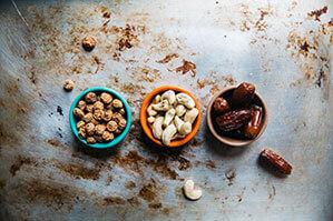 Drei kleine Schüsseln mit getrockneten Snacks und Nüssen gefüllt