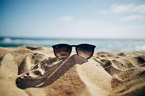 Sonnenbrille auf Sand am Strand, Meer im Hintergrund