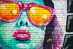Wand mit Graffitibild von Frau mit pinker Sonnenbrille