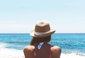 Frau im Bikini sitzt am Strand und schaut auf Meer, mit Sonnenhut