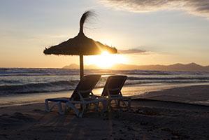 Sonnenschirm mit Liegestühlen im Sonnenuntergang