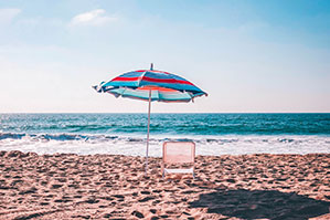 Sonnenschirm am Strand mit Liegestuhl