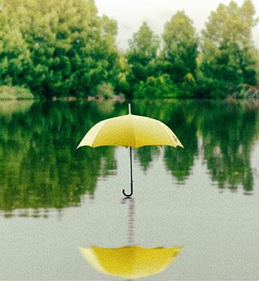 Gelber Stockschirm schwebt auf Wasser