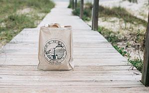 Naturfarbene Stofftasche bedruck auf einem Strandsteg