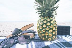 Stranddecke auf der eine Sonnenbrille, eine Ananas, Lautsprecher und Sandalen liegen