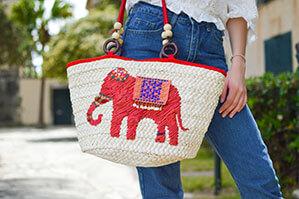 Beige farbene Strandtasche mit einem roten Elefant und an den roten Hänkeln sind zwei Perlen eingearbeitet